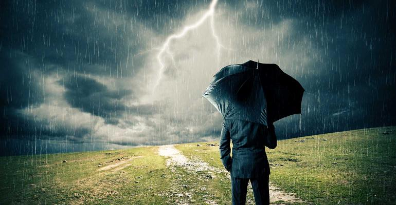 businessman with umbrella in stormy weather