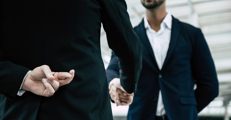 businessmen shaking hands with fingers crossed