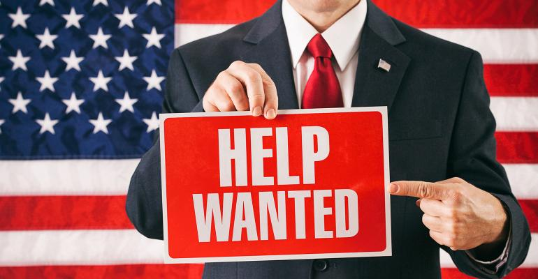 man holding help wanted sign in front of US flag